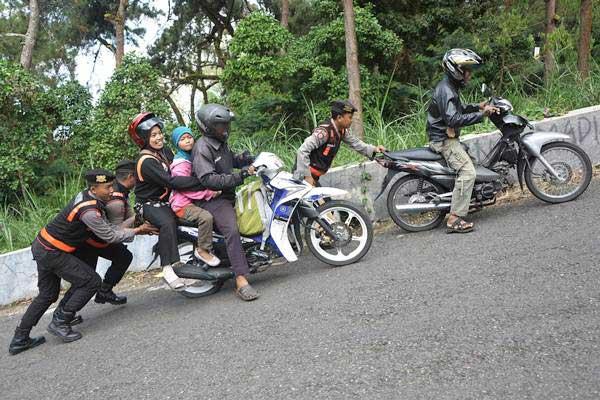 Petugas kepolisian membantu mengganjal ban dan mendorong kendaraan di tanjakan Mojosemi, Sarangan, Magetan, Jawa Timur. - Antara/Fikri Yusuf
