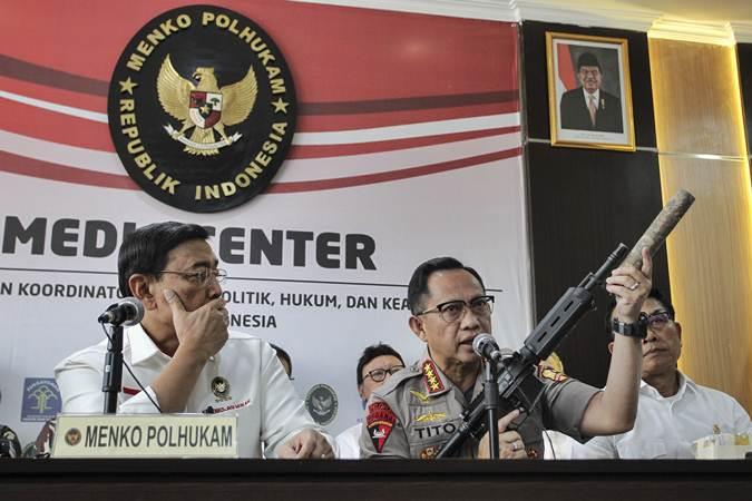 Kapolri Jenderal Pol Tito Karnavian (tengah) disaksikan Menko Polhukam Wiranto (kiri) dan Kepala KSP Moeldoko (kanan) menunjukkan barang bukti senjata api saat menyampaikan konferensi pers perkembangan pascakerusuhan di Jakarta dini hari tadi, di kantor Kemenko Polhukam, Jakarta, Rabu (22/5/2019). - ANTARA/Dhemas Reviyanto