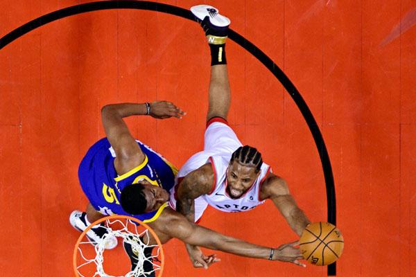 Forward Toronto Raptors Kawhi Leonard (2) menembakkan bola, coba dihadang center Golden State Warriors Kevon Looney (5) pada gim pertama final NBA di Toronto, Kanada. - Reuters