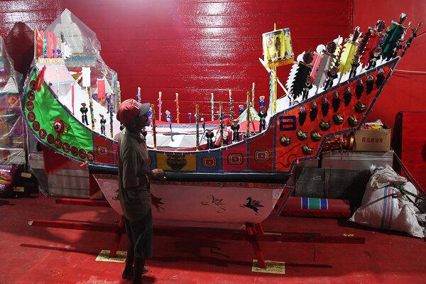 Seorang pengunjung melihat replika perahu tongkang yang akan dibakar setelah puncak perayaan ulang tahun Dewa Tio Hu Guan Sue di Klenteng Hai Cu King Desa Sungai Bakau, Rokan Hilir, Riau, Sabtu (18/5/2019). Budaya peranakan salah satu daya tarik wisata di Riau. - Antara/Aswaddy Hamid