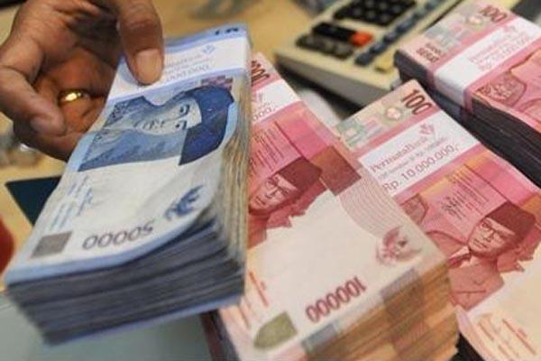 Ilustrasi - Seorang karyawan bank tengah merapikan uang - Antara