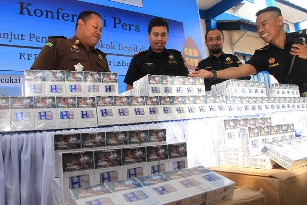 Kepala Kantor Pengawasan dan Pelayanan Bea dan Cukai Meulaboh Akbar Harfianto (kedua kiri) didampingi Kasi Pidsus Kejaksaan Negeri Simeuleu Mulyadi (kiri) memperlihatkan rokok ilegal saat konferensi pers di Kantor Pengawasan dan Pelayanan Bea dan Cukai Tipe Madya Pambean C Meulaboh, Aceh Barat, Aceh, Selasa (12/3/2019). - ANTARA