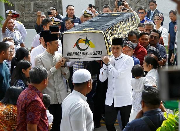 Putra Ibu Negara 2004-2014 Ani Yudhoyono, Agus Harimurti Yudhoyono (kiri) dan Edhie Baskoro Yudhoyono memanggul keranda jenazah Ibunda untuk dimandikan di KBRI Singapura, Sabtu (1/6/2019). - Reuters/Feline Lim