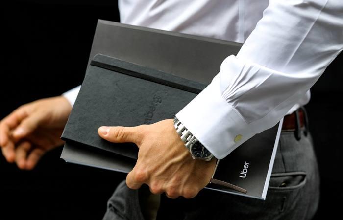 Seorang investor tengah berjalan dengan membawa dokumen IPO Uber di Manhattan, New York. AS (30/4/2019). - Reuters/Jeenah Moon