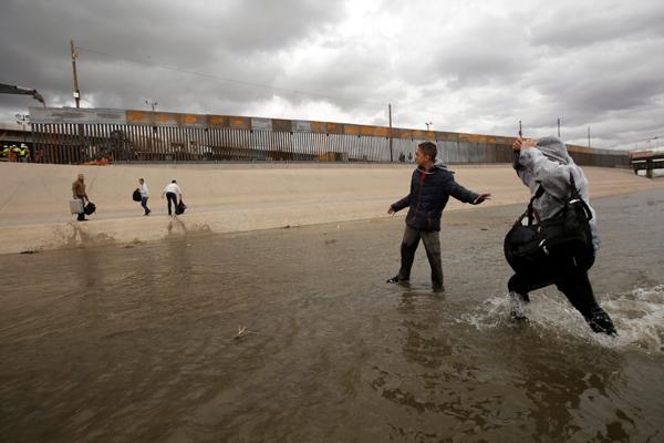Para imigran menyeberangi sungai di dekat proyek pembangunan tembok perbatasan antara El Paso dan Ciudad Juarez, Meksiko, Selasa (5/2/2019). - Reuters/Jose Luis Gonzalez