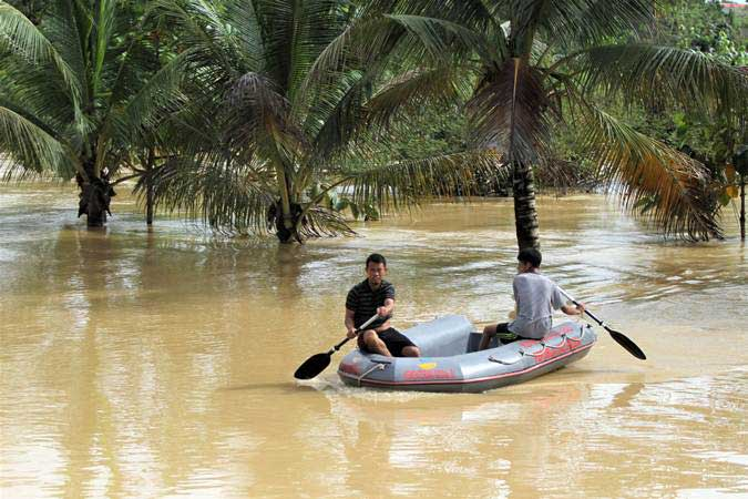 Dua warga menerobos banjir dengan mengunakan perahu milik Dinas Sosial Provinsi Sulawesi Tenggara saat banjir bandang yang terjadi di permukiman di Kelurahan Wanggu, Kendari, Sulawesi Tenggara, Senin (10/6/2019). - ANTARA/Jojon