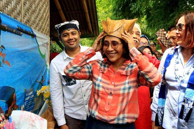 Menteri Kelautan dan Perikanan Susi Pudjiastuti (kedua kanan) memakai topi dari bahan sampah laut hasil kreasi nelayan setempat di Bangsring, Banyuwangi, Jawa Timur, Selasa (2/4/2019). - ANTARA/Budi Candra Setya