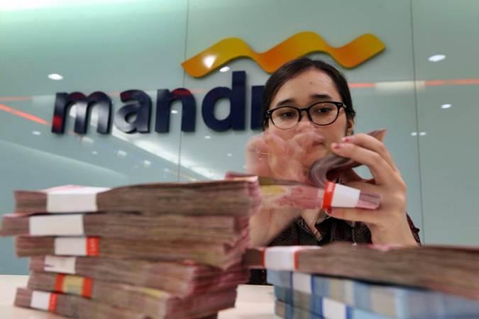 Karyawati menghitung uang pecahan Rp100.000 di salah satu kantor cabang milik Bank Mandiri, di Jakarta, Rabu (12/6/2019). - Bisnis/Nurul Hidayat
