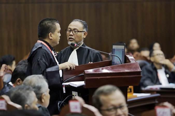 Kuasa hukum Calon Presiden dan Wakil Presiden nomor urut 02 selaku pemohon Bambang Widjojanto (kanan) dan Denny Indrayana (kedua kanan) berbincang di sela-sela pembacaan gugatan sidang perdana Perselisihan Hasil Pemilihan Umum (PHPU) sengketa Pilpres 2019 di Mahkamah Konstitusi, Jakarta, Jumat (14/6/2019). - Bisnis/Felix Jody Kinarwan