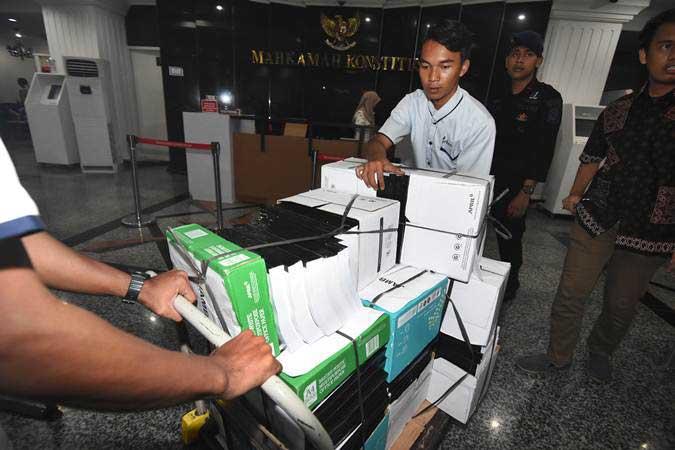 Petugas mengangkut berkas bukti gugatan Badan Pemenangan Nasional (BPN) Prabowo-Sandi di Gedung Mahkamah Konstitusi, Jakarta, Kamis (13/6/2019). - ANTARA/Indrianto Eko Suwarso