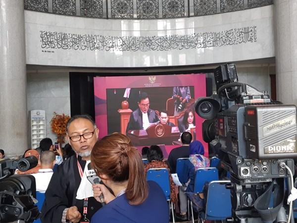 Ketua Tim Hukum Paslon 02 Bambang Widjojanto melayani wawancara stasiun televisi saat Ketua Kuasa Hukum Paslon 01 Yusril Ihza Mahendra membacakan jawaban, Selasa (18/6/2019). - Bisnis/Feni Freycinetia Fitriani