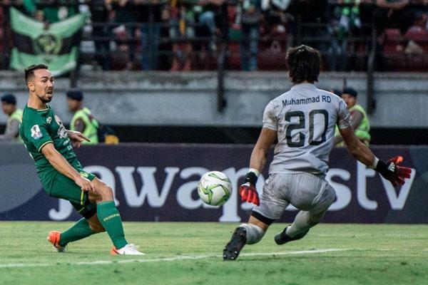Tendangan gelandang Persevaya Surabaya Damian Lizio ditepis kiper Madura United Muhammad Ridho Djazulie. - Persebaya.id