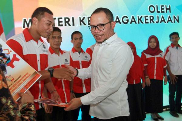 Menteri Tenaga Kerja Hanif Dhakiri (kanan) menyerahkan secara simbolis seribu sertifikat kelulusan kepada perwakilan siswa Balai Latihan Kerja (BLK) di Makassar, Sulawesi Selatan, Rabu (17/10/2018). - JIBI/Paulus Tandi Bone