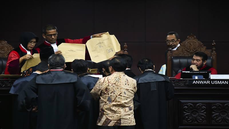 Ketua Mahkamah Konstitusi Anwar Usman (kanan) bersama Hakim Konstitusi Saldi Isra (kedua kiri) dan Enny Nurbaningsih (kiri) melakukan pengecekan alat bukti sampul surat suara dari pihak termohon atau KPU dan dari pihak pemohon atau Tim hukum Badan Pemenangan Nasional (BPN) pasangan Calon Presiden dan Calon Wakil Presiden nomor urut 02 saat sidang lanjutan Perselisihan Hasil Pemilihan Umum (PHPU) presiden dan wakil presiden di gedung Mahkamah Konstitusi, Jakarta, Kamis (20/6/2019). - Antara