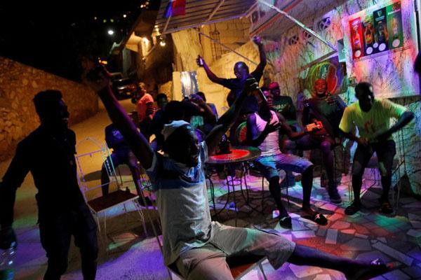 Warga Port au Prince, ibu kota Haiti, yang menggelar nonton bareng, kegirangan setelah tim nasional mereka menjebol gawang Kosta Rika di Gold Cup di Amerika Serikat. - Reuters/Andres Martinez Casares