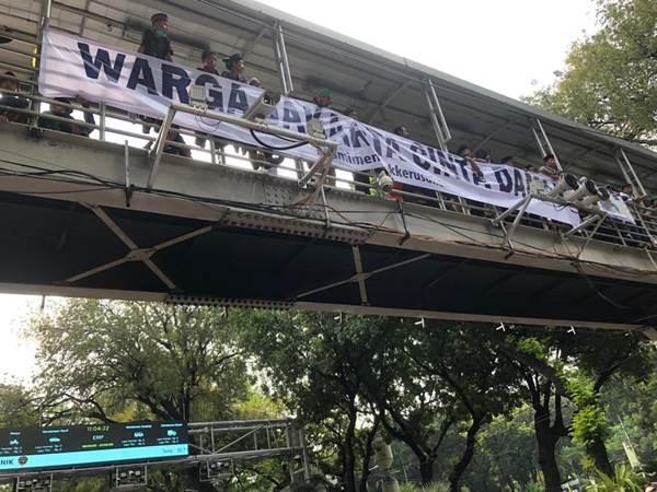 Warga menyaksikan aksi massa dari Jembatan Penyeberangan Orang - Bisnis/Sholahuddin Al Ayyubi