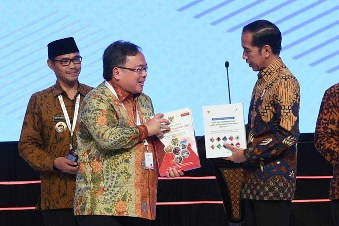 Presiden Joko WIdodo (kanan) menerima buku rancangan awal Rencana Kerja Pemerintah (RKP) tahun 2020 dan Rencana Pembangunan Jangka Menengah Nasional (RPJMN) 2020-2024 dari Menteri PPN/Kepala Bappenas Bambang Brodjonegoro saat membuka acara Musyawarah Perencanaan Pembangunan Nasional (Musrenbangnas) 2019 di Jakarta, Kamis (9/5/2019). - ANTARA/Wahyu Putro A