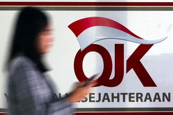 Karyawan melintas di dekat logo Otoritas Jasa Keuangan (OJK) di Jakarta, Senin (13/5/2019). - Bisnis/Abdullah Azzam
