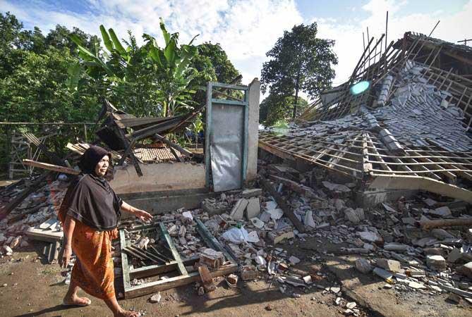 Warga melintas di dekat rumah yang roboh akibat gempa bumi di Desa Pesanggrahan, Kecamatan Montong Gading, Selong, Lombok Timur, NTB, Senin (18/3/2019). - ANTARA/Ahmad Subaidi