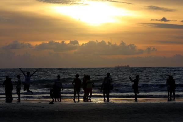 Wisatawan menikmati suasana matahari terbenam di Pantai Kuta, Bali - JIBI/Rachman