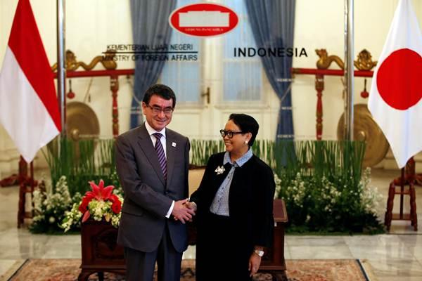 Menteri Luar Negeri Retno Marsudi (kanan) berjabat tangan dengan Menteri Luar Negeri Jepang Taro Kono, menjelang pertemuan di Jakarta, Senin (25/6/2018). - Reuters/Darren Whiteside