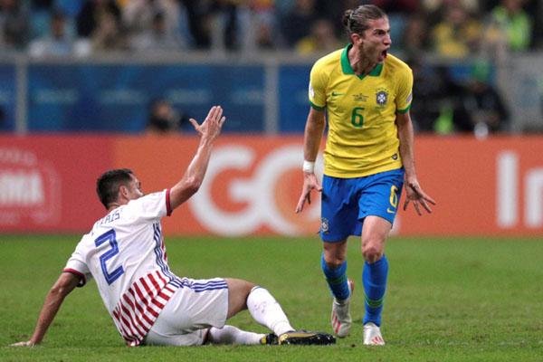 Reaksi bek Brasil Filipe Luis (kanan) dan bek Paraguay Ivan Piris. - Reuters/Ueslei Marcelino