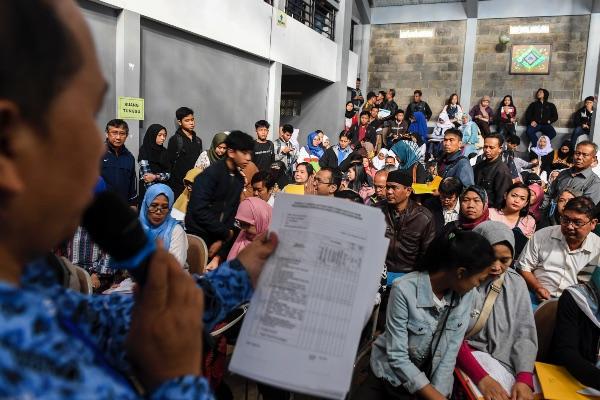Orangtua dan calon siswa mengantre saat pendaftaran Penerimaan Peserta Didik Baru (PPDB) 2019 tingkat SMA-SMK di SMAN 2 Bandung, Jawa Barat, Senin (17/6/2019). - ANTARA FOTO/M. Agung Rajasa