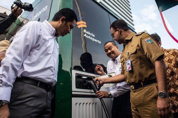 Gubernur DKI Jakarta Anies Baswedan (kanan) didampingi Dirut TransJakarta Agung Wicaksono (kedua kanan) dan Direktur Operasional TransJakarta Daud Joseph (kiri) mengisi daya ke bus listrik saat uji coba di halaman Balai Kota, Jakarta, Senin (29/4/2019). Pemprov DKI Jakarta bersama PT TransJakarta dan PT Bakrie & Brother Tbk menyelenggarakan uji coba bus listrik yang bertujuan untuk memastikan penggunaan kendaraan listrik sebagai alat transportasi umum di Jakarta.  - ANTARA