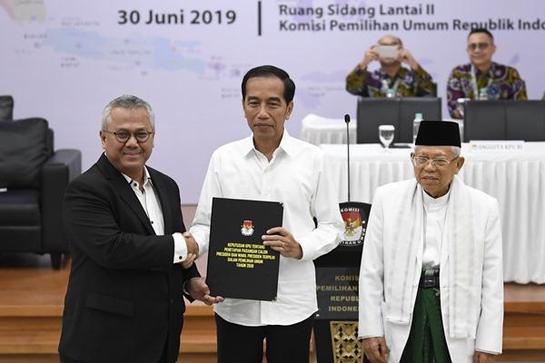 Ketua KPU Arief Budiman (kiri) menyerahkan surat keputusan KPU tentang Penetapan Hasil Pemilu 2019 kepada Presiden dan Wakil Presiden terpilih periode 2019-2024, Joko Widodo (tengah) dan KH Ma'ruf Amin (kanan) di gedung KPU, Jakarta, Minggu (30/6/2019). - ANTARA/Puspa Perwitasari