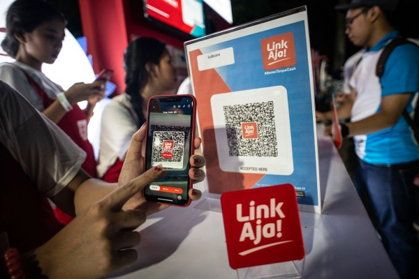 Pengunjung melakukan transaksi menggunakan layanan keuangan berbasis elektronik LinkAja saat peluncuran di Kompleks Gelora Bung Karno, Senayan, Jakarta, Minggu (30/6/2019). - ANTARA FOTO/Aprillio Akbar