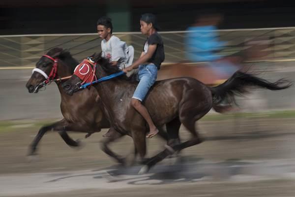 Dua remaja melatih kudanya berkenaan dengan kegiatan Parade 1001 Kuda dan Festival Tenun Ikat. - Antara/Nyoman Budhiana