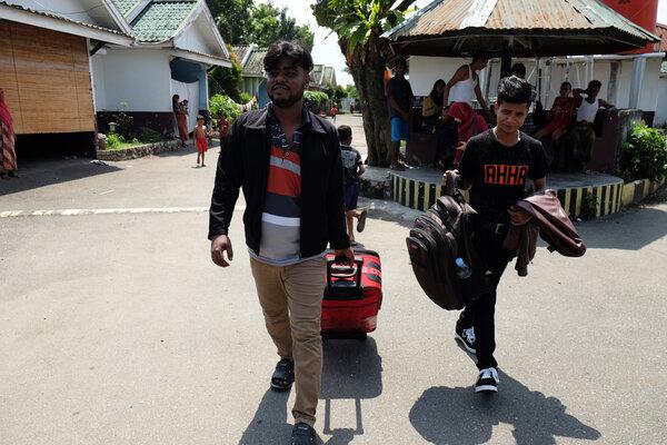 Pengungsi etnis Rohingya, Myanmar Hasan Ali (kanan) dibantu rekannya sesama pengungsi membawa barang-barangnya saat akan berangkat ke bandara untuk diterbangkan ke Amerika Serikat di lokasi penampungan, Medan, Sumatera Utara, Rabu (19/6/2019). Sebanyak enam pengungsi asal Afghanistan dan Myanmar di bawah naungan United Nations High Commissioner for Refugees (UNHCR) diterbangkan ke lokasi penampungan di Amerika Serikat. - Antara/Irsan Mulyadi