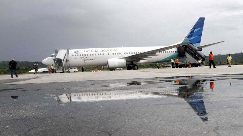 Penumpang bersiap menaiki pesawat maskapai penerbangan Garuda Indonesia di Bandara Frans Kaisiepo Biak, Papua, Selasa (29/10/2013).  - Bisnis/Dwi Prasetya