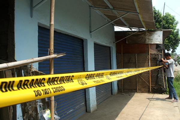 Pewarta mengabadikan toko yang terpasang garis polisi pasca penggerebekan terduga pelaku teroris, di kawasan Babelan, Kabupaten Bekasi, Jawa Barat, Minggu (5/5/2019)./ANTARA - Risky Andrianto