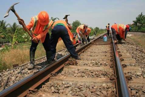 Para pejerja memperbaiki jalur kereta api