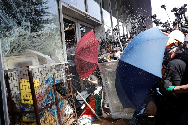 Pengunjuk rasa yang menggunakan payung mencoba masuk ke gedung Dewan Legislatif Hong Kong, Senin (1/7/2019). Unjuk rasa besar-besaran kembali terjadi di kota pelabuhan itu pada hari peringatan 20 tahun penyerahan Hong Kong dari Inggris ke China. - Reuters/Tyrone Siu