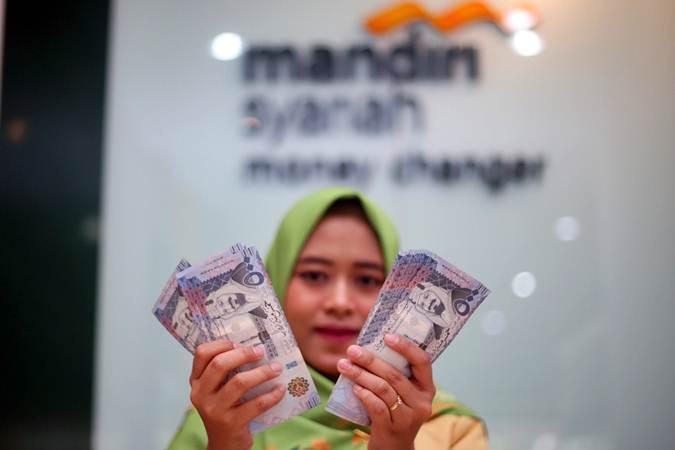 Karyawan menunjukkan mata uang Riyal di Money Changer Mandiri Syariah Thamrin, Jakarta, Selasa (2/7/2019). - Bisnis/Abdullah Azzam