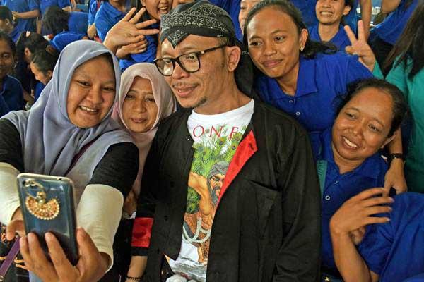 Menaker M Hanif Dhakiri (tengah) berswafoto bersama para Tenaga Kerja Indonesia (TKI) saat Peringatan Buruh Migran Internasional di Gedung Kesenian Kabupaten Ponorogo, Jawa Timur, Senin (18/12). - ANTARA/Siswowidodo