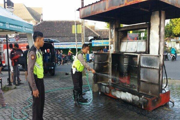 Petugas kepolisian menyiram air di pertamini di Jl. Sultan Agung, Kelurahan Nologaten, Kecamatan Ponorogo, yang terbakar, Senin (8/7/2019). - Ist