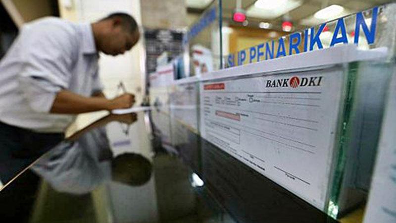 Nasabah mengisi blangko penarikan uang di Bank DKI, Jakarta, Selasa (27/1/2015) - Bisnis /Abdullah Azzam