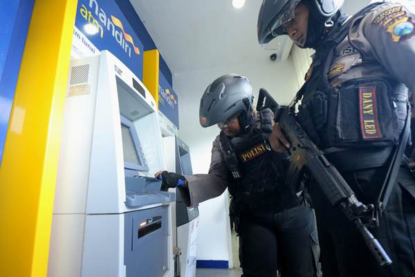 Polisi memeriksa mesin Anjungan Tunai Mandiri (ATM) Bank Mandiri, guna mengantisipasi kejahatan 'skimming', di Surabaya, Jawa Timur, Selasa (20/3/2018). - ANTARA/Didik Suhartono