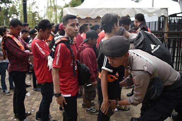 Seorang anggota Polisi memeriksa barang bawaan penonton pertandingan Liga-1 Persija Jakarta melawan Persib Bandung di Stadion Utama Gelora Bung Karno (GBK) Senayan, Jakarta, Rabu (10/7/2019). - ANTARA FOTO/M Risyal Hidayat