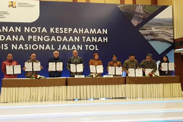 Kepala Badan Pengatur Jalan Tol Danang Parikesit (keempat kiri) dan Direktur Utama LMAN Rahayu Puspasari (kelima kiri) menunjukkan nota kesepahaman pengembalian dana talangan lahan tol. - Rivki Maulana