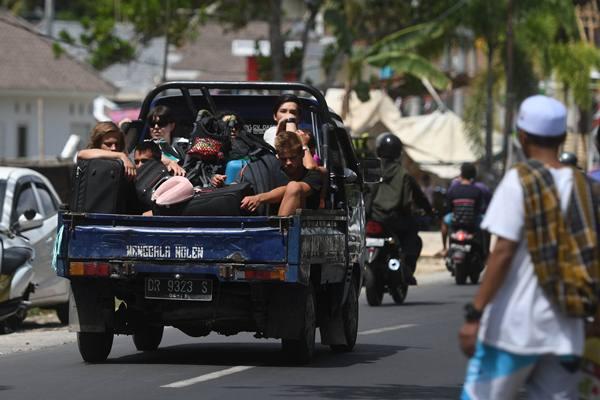 Sejumlah wisatawan mancanegara menumpang mobil bak terbuka ketika menuju Mataram di Lombok Utara, NTB, Senin (6/8). Sedikitnya 700 orang wisatawan bersama warga setempat dievakuasi dari Gili Trawangan, Gili Air dan Gili Meno menuju Pelabuhan Bangsal mengantisipasi terjadinya gempa susulan. - Antara