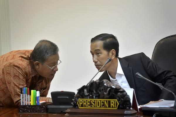 Presiden Joko Widodo (kanan) berdiskusi dengan Menko Perekonomian Darmin Nasution saat memimpin Rapat Kabinet Terbatas membahas pemanfaatan ruang udara selatan Pulau Jawa di Kantor Kepresidenan, Jakarta, Jumat (8/1). - Antara