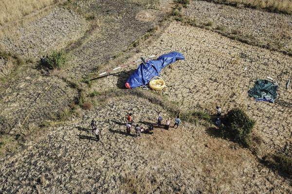 Sejumlah warga bersama petugas berada dekat pesawat helikopter yang jatuh di Dusun Gilik, Desa Kawo, Kecamatan Pujut, Lombok Tengah, NTB, Senin (15/7/2019). Persawahan kering yang merupakan lokasi jatuhnya pesawat helikopter B206L4 PKCDV ramai dikunjungi warga yang ingin mengabadikan peristiwa itu. - Antara/Ahmad Subaidi