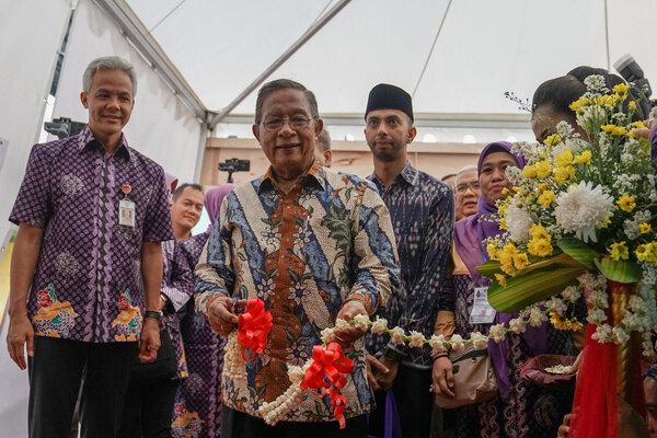 Menteri Kordinator Bidang Perekonomian Darmin Nasution (tengah), memotong pita tanda dibukanya ekspo produk koperasi dan UMKM, pada acara peringatan Hari Koperasi Nasional, di GOR Satria Purwokerto, Banyumas, Jateng, Jumat (12/7/2019). - Antara/Idhad Zakaria