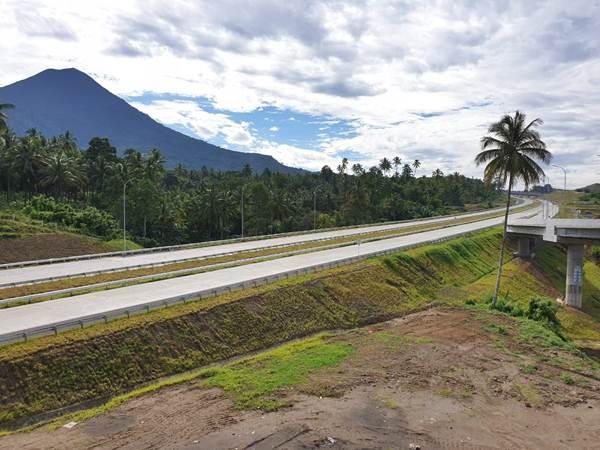 Suasana jalan tol Manado-Bitung dengan latar belakang Gunung Klabat pada Jumat (5/7/2019). Keberadaan jalan tol ini diharapkan memacu investasi di Sulawesi Utara terutama di KEK Bitung. - Bisnis/Lukas Hendra