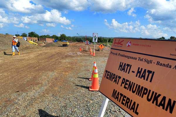 Pekerja beraktivitas di proyek pembangunan jalan tol Banda Aceh-Sigli di kawasan Blangbintang, Kabupaten Aceh Besar, provinsi Aceh, Selasa (15/1/2019). - ANTARA FOTO/Ampelsa