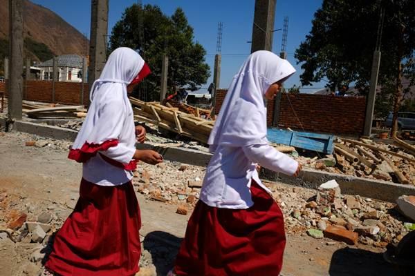 Siswa melintas di samping pembangunan gedung sekolah yang roboh akibat gempa di Sembalun, Lombok Timur, NTB, Rabu (24/10/2018). - JIBI/Felix Jody Kinarwan